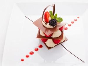 Un original postre con laminas de chocolate y frutas