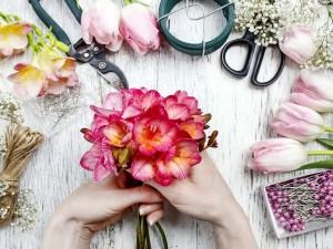 Mujer formando un ramo con fresias y tulipanes