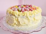 Un pastel cubierto con buttercream y decorado con golosinas