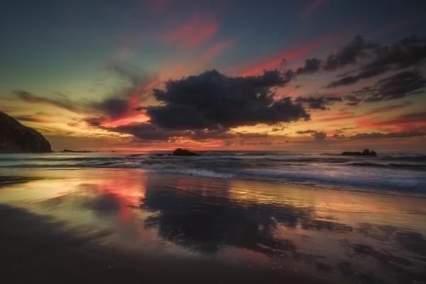Hermoso cielo al amanecer reflejado en la orilla de una playa
