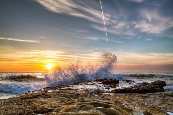 Olas chocando contra las rocas al amanecer