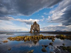 Nubes sobre una formación rocosa en el mar