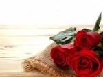Tres rosas rojas sobre una mesa