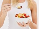 Mujer comiendo una ensalada de frutas