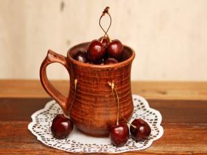 Cerezas en una taza de madera
