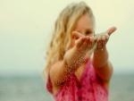 Niña con arena en las manos