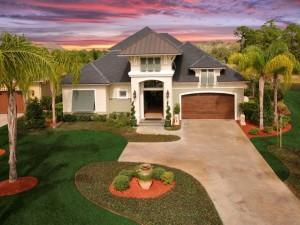 Casa con cesped y palmeras en el jardín