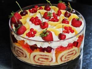 Un postre con frutas frescas, bizcocho y nata