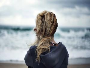 Mujer contemplando el mar en un día de viento
