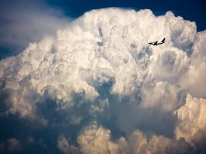 Un avión volando junto a una masa nubes