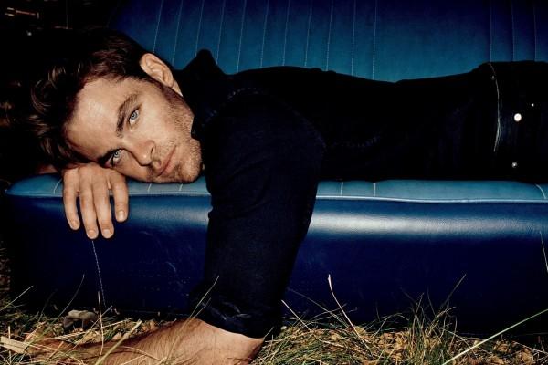 Chris Pine tumbado en un sofá azul