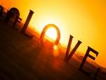 El sol detrás de grande letras que forman la palabra amor