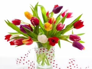Bellos tulipanes en un recipiente de vidrio
