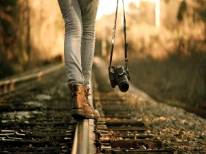 Caminando en equilibrio sobre la vía del ferrocarril con una cámara Canon