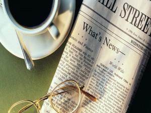 Taza de café junto a un diario y unas gafas