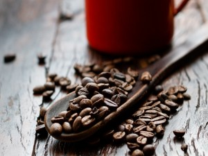 Granos de café sobre una cuchara de madera