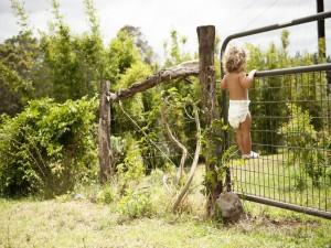 Un bebé trepado a una cerca