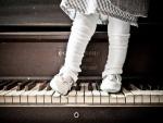 Una bebé sobre las teclas de un piano
