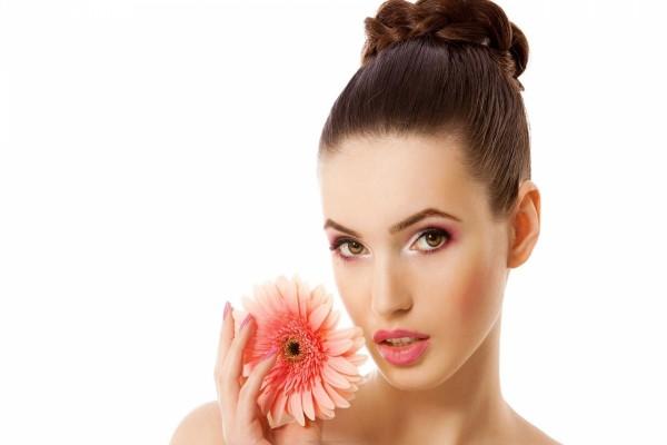 Bella mujer con una flor rosa