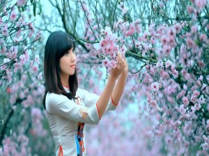 Chica observando las flores de un árbol
