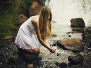 Mujer rubia tomando agua del río
