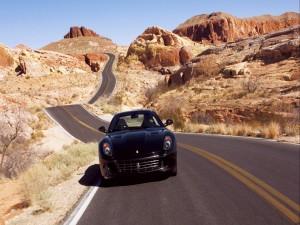 Ferrari negro circulando por una bonita carretera