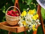 Ramo de flores y una cesta con fresas sobre una silla