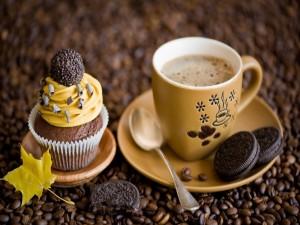 Café acompañado de un cupcake y unas galletas oreo