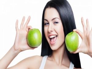 Mujer con una manzana verde en cada mano