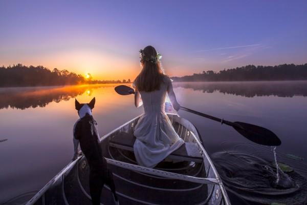 Mujer con un perro remando en un bote al amanecer