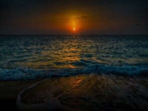 Lejano sol iluminando la orilla del mar