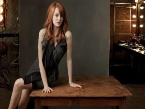 La guapa actriz Emma Stone sentada en una mesa de madera