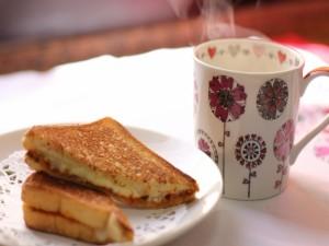 Un sándwich caliente de queso junto a una taza humeante