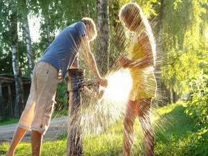 Una pareja jugando con el agua de una fuente