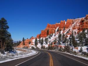Rocas y árboles con nieve junto a una carretera
