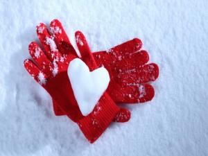 Un corazón de nieve sobre unos guantes de color rojo