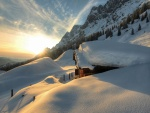 Los rayos del sol iluminan una casa cubierta de nieve
