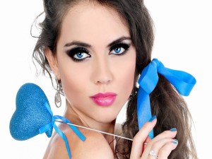 Chica con ojos azules sosteniendo un corazón azul