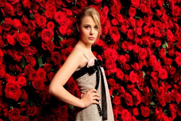 La actriz Chloë Moretz junto a una pared de rosas rojas