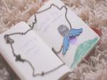 Collar con alas de ángel sobre un cuento