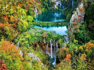 Río cayendo en cascadas entre rocas y árboles otoñales