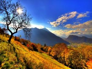 Sol iluminando las montañas y el valle en otoño
