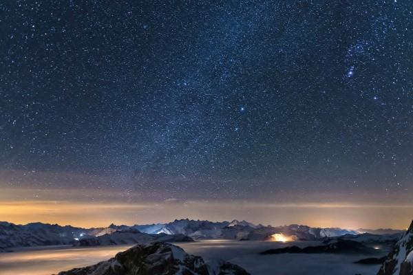 Cielo estrellado sobre montañas cubiertas de nieve