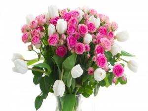 Ramo de rosas de color rosa y tulipanes blancos en un florero de cristal
