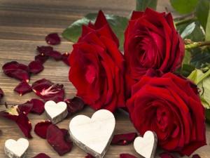 Corazones blancos tallados en madera junto a unas rosas rojas