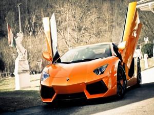 Un Lamborghini naranja con las puertas abiertas