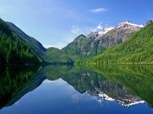 Postal: Cielo y montañas reflejadas en un tranquilo lago