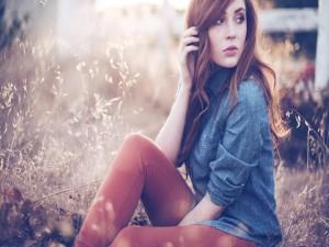 Chica con camisa vaquera sentada en el campo