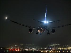 Avión a punto de aterrizar en una pista iluminada