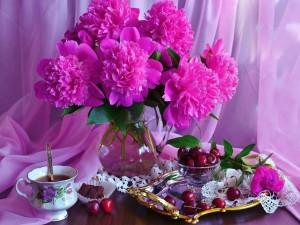Peonías de color fucsia junto a una taza de té y cerezas